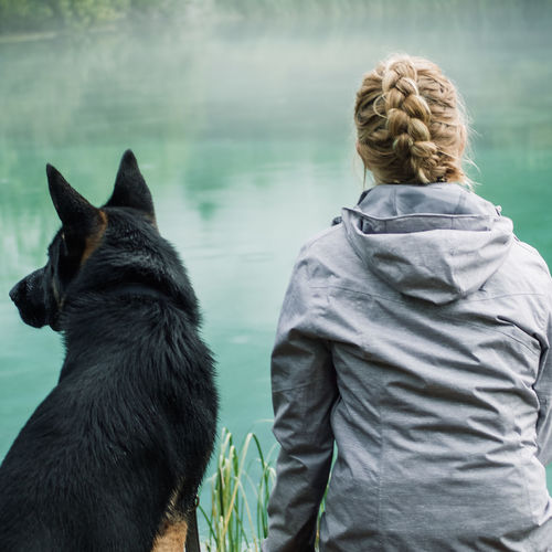 Rear view of woman with dog looking at view