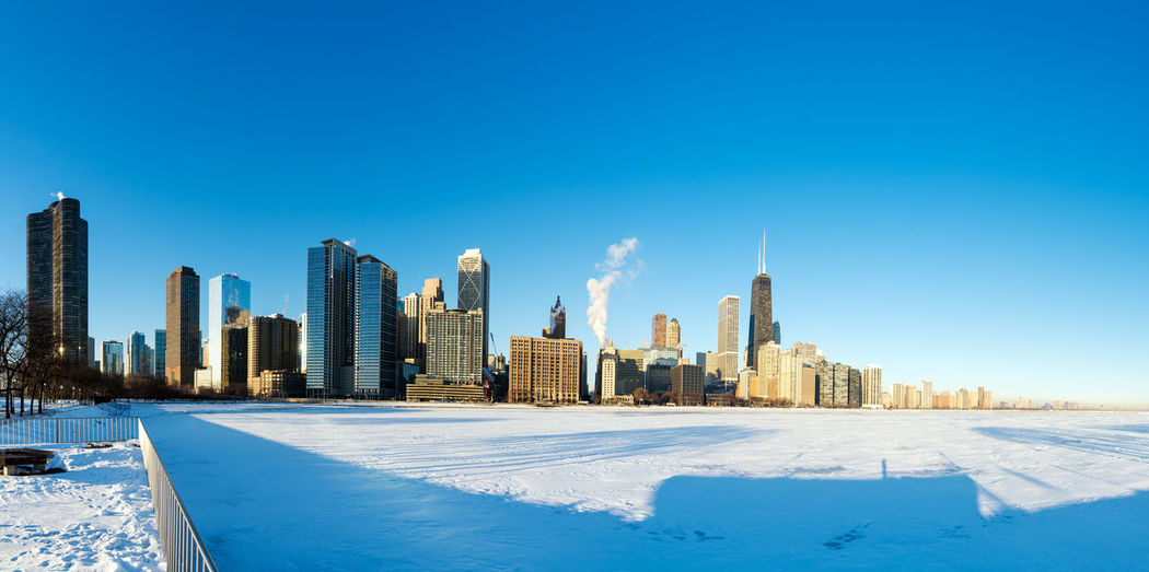 Modern Skyscrapers By Frozen Lake Michigan Against Blue Sky