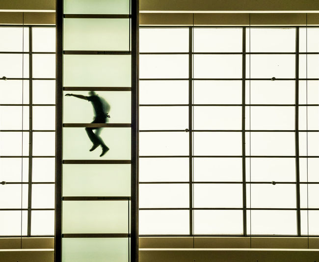 Directly below shot of man lying on roof seen through glass