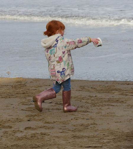 Street Photograhpy Streetlife Young Girl Beach Sea Seaside Playing Outdoors Colourful Sand Cute Fashion Sparkly Wellies Candid Gingerhair