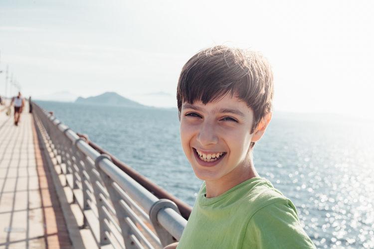 Portrait Of Smiling Boy Against Sea