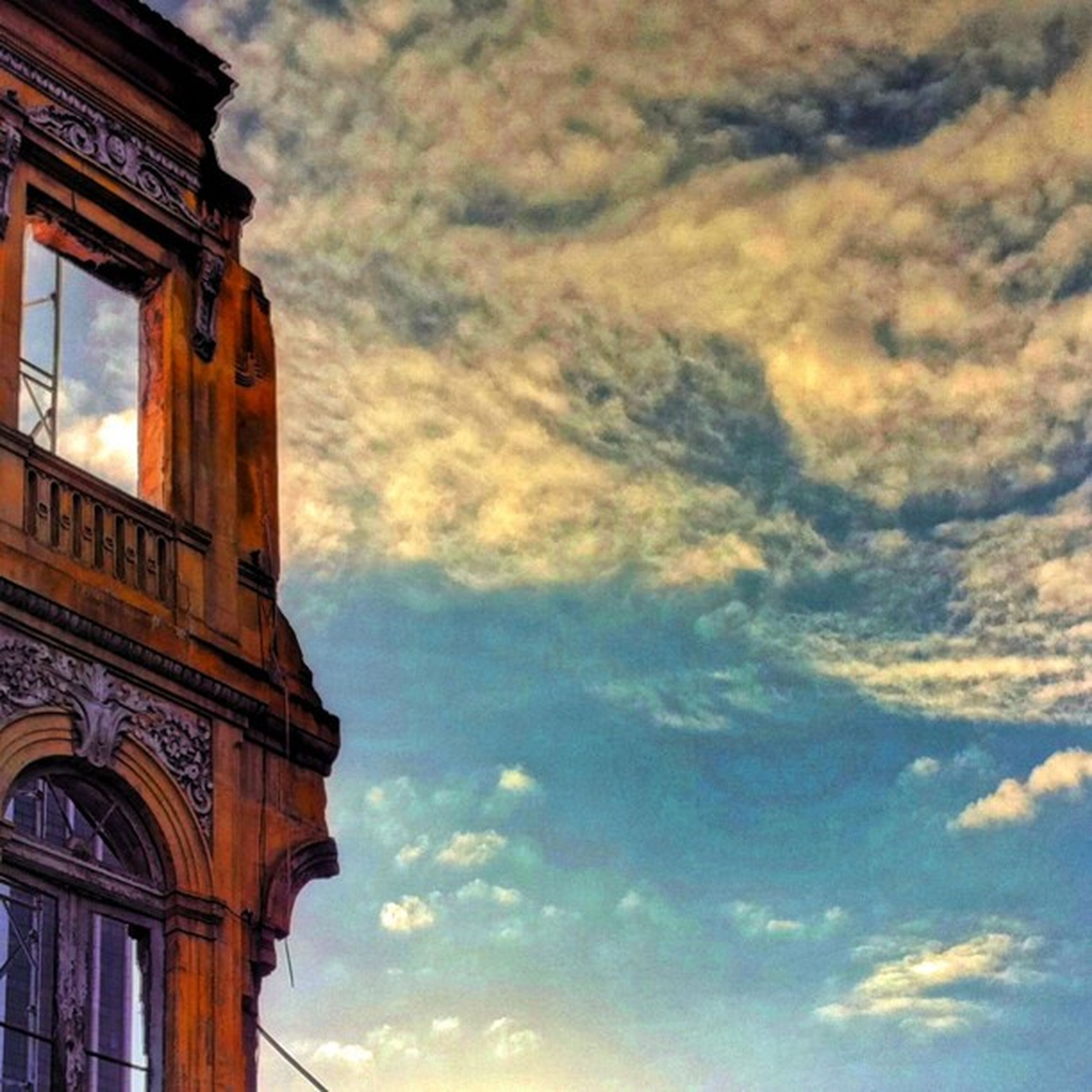 architecture, built structure, low angle view, sky, building exterior, cloud - sky, window, cloudy, cloud, building, high section, no people, outdoors, day, part of, residential structure, arch, facade, city, house