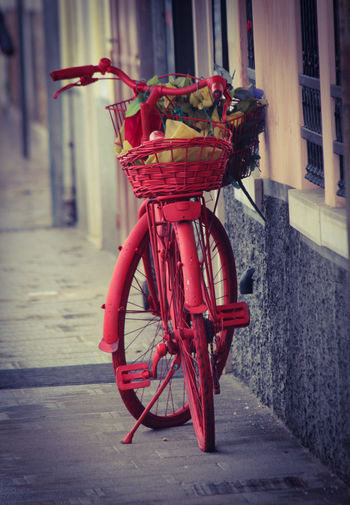 Red bicycle on footpath by street
