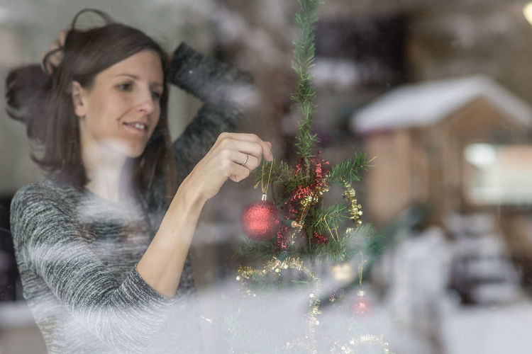 Portrait of smiling young woman holding christmas tree during winter