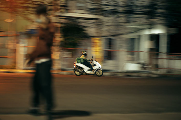 Blurred motion of people riding motorcycle on road