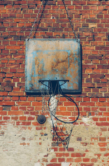 View of basketball hoop against brick wall