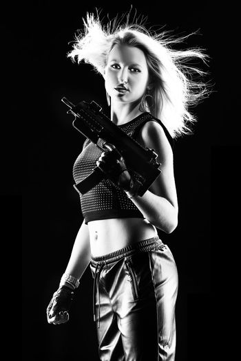Portrait Of Young Woman Holding Gun Against Black Background