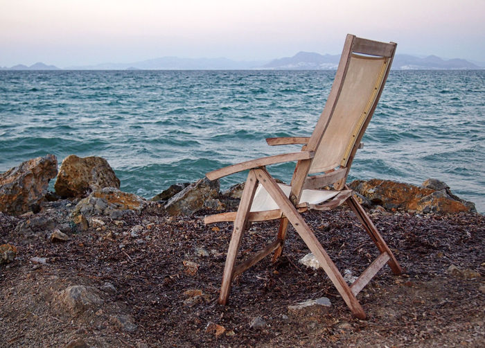 an entry chair by the sea in twilight Twilight Beach Beauty In Nature Chair Conceptual Day Easel Horizon Horizon Over Water Land Nature No People Nobody Non-urban Scene Outdoors Scenics - Nature Sea Seat Sky Tranquil Scene Tranquility Water Wood - Material