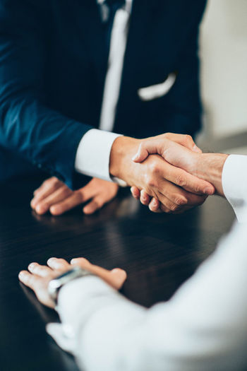 Midsection of business people giving handshake at desk in office