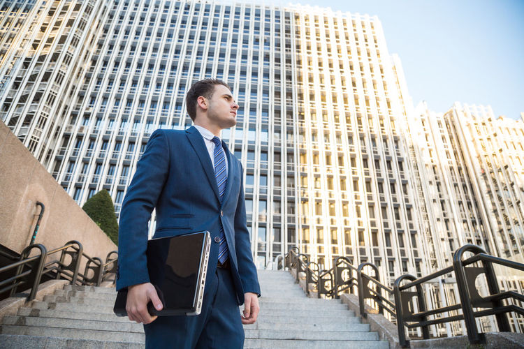 Low Angle View Of Businessman Standing Against Office Building