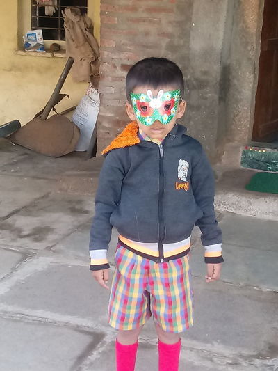 Full length portrait of boy standing by mask