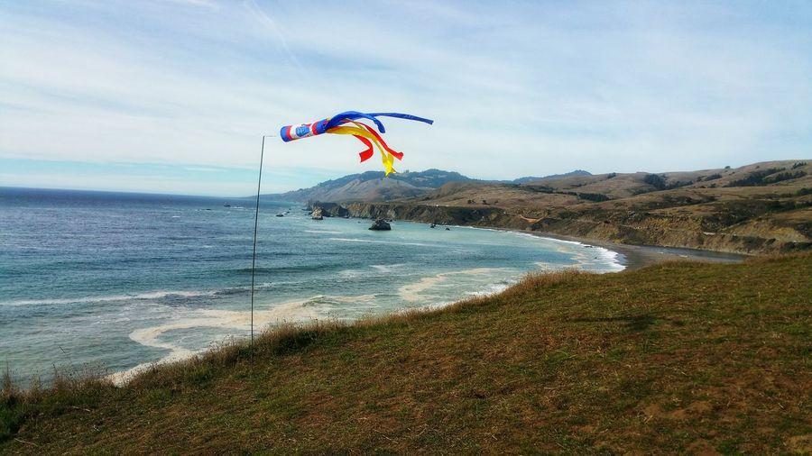 Windsock. Wind Direction for tak I ng flight. Cliffs above ocean. Windsock Movement Wind Lifting Red Blue Stripes Ocean Cliffs Directional Sport Paragliding Zen Countryside Background Curved  Golden Grasses Autumn Water Sea Flying Beach Sand Mid-air Fun Motion Rushing Paragliding Surf