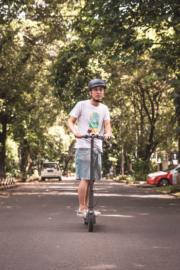 Portrait Of Mid Adult Man Riding Push Scooter On Road Against Trees