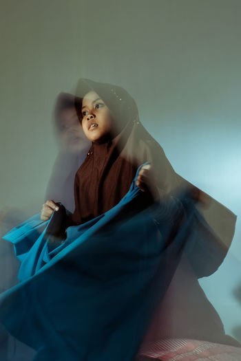 Blurred motion of girl holding fabric