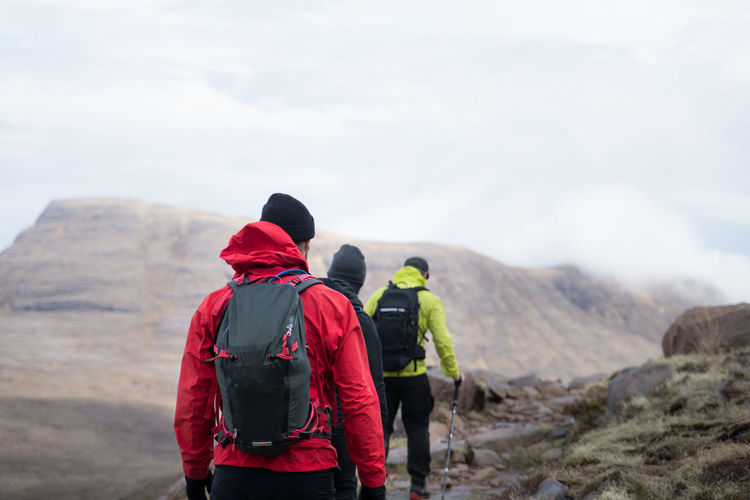 Rear view of male hikers hiking on mountain against cloudy sky