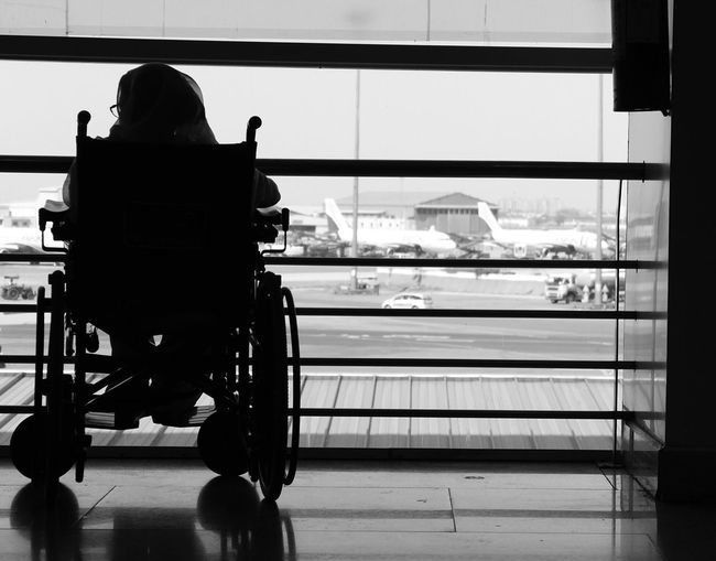 Rear view of disabled woman sitting on wheelchair against window