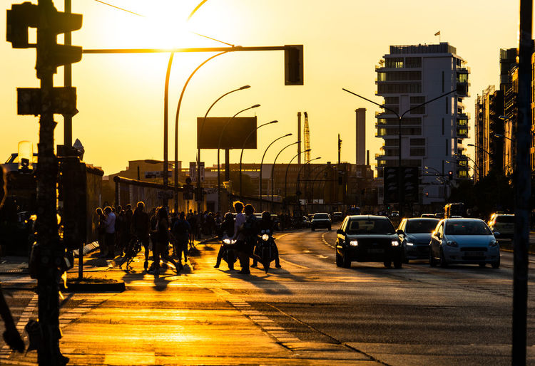 People walking on city street against sky during sunset