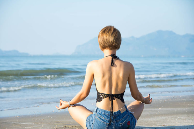 Rear View Of Young Woman Doing Yoga At Beach