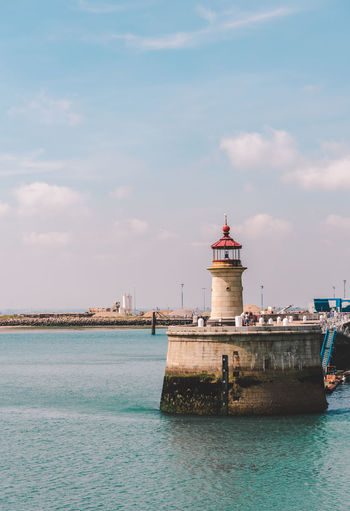 Lighthouse Building City Day Urban Building Sky Clouds Lighthouse Colours Beach Water Nautical Vessel Nautical Equipment Sea Lighthouse Harbor Beach Sunset Sky Architecture Coastline Rocky Coastline Coastal Feature Seascape Ocean Calm Lookout Tower Pier