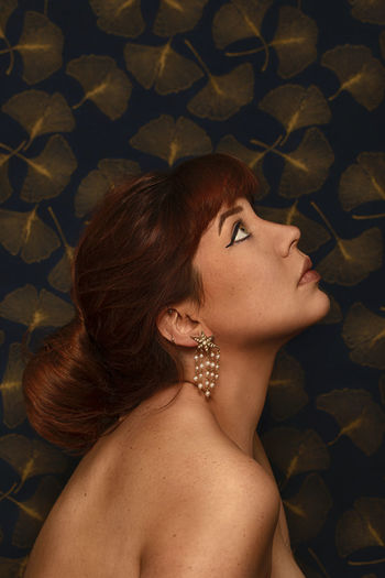 Side view of woman looking up against abstract background