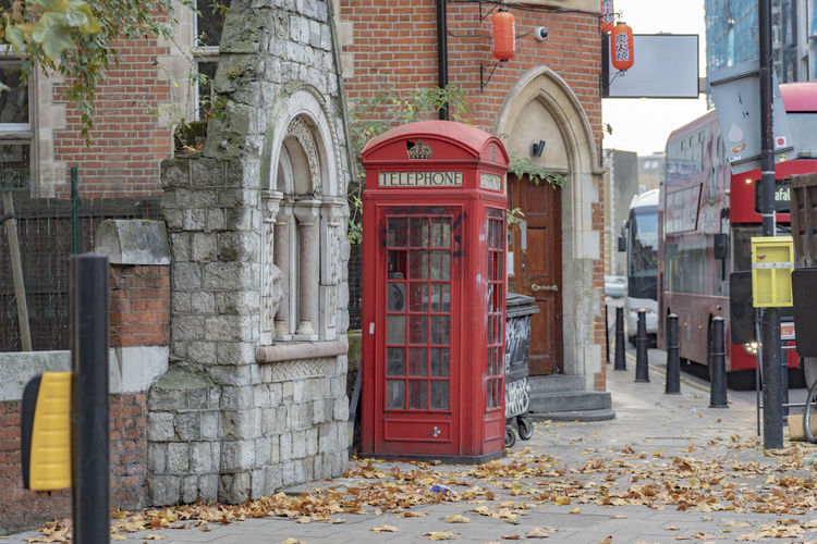 Architecture Red City Telephone Booth Day Autumn Telephone Communication Street Leaf Arch History The Past London Symbol Quintessential Red Telephone Box Red Telephone Booth Double Decker Bus England No People Outdoors Building Exterior Stone Wall Stone