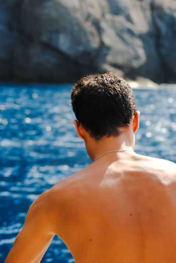 Rear view of shirtless boy in sea