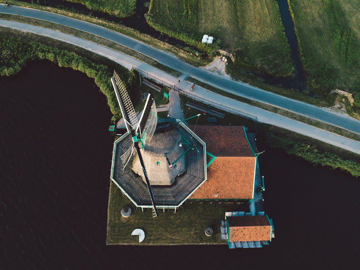 Aerial View Of Windmill Over Lake By Road