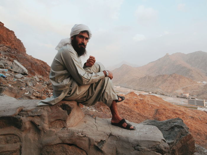 Pakistani on Jabal Hills , Macca Sitting Full Length Desert Sky Sand Dune Hiker Namib Desert Camel Atmospheric Egyptian Culture Bridle Saddle Working Animal Rajasthan Pyramid Marram Grass Barren Arid Ancient Civilization Civilization Arid Climate Ancient Egyptian Culture Turban Archaeology Ancient Rome Arid Landscape