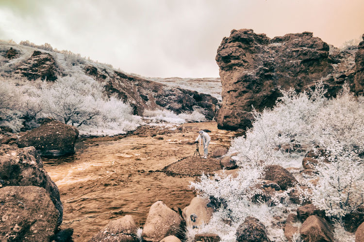 Rocks on snow covered landscape against sky