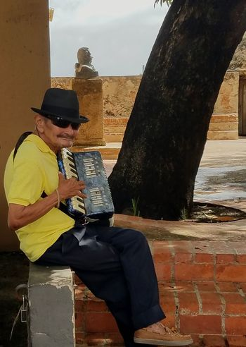 Sitting Hat Adult Outdoors One Man Only Cityscape One Person People Peole Of San Juan People Watching Walking Around The City  Colorful City Open Edit Street Musician Popular Photos San Juan PR Snap a Stranger Who What Where Enjoy The New Normal Take Over Music Business Stories
