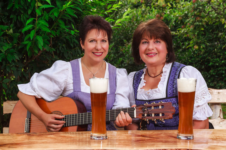 Two bavarian women in the dirndl, sitting at a table in the garden, play music and sing together - Ruperti-Zwoagsang, Music Singing Alcohol Beer - Alcohol Beer Glass Dirndl Drink Drinking Drinking Glass Folk Music Food And Drink Friendship Guitar Leisure Activity Looking At Camera Outdoors Portrait Refreshment Sitting Smiling Table Togetherness Two People White Beer Women