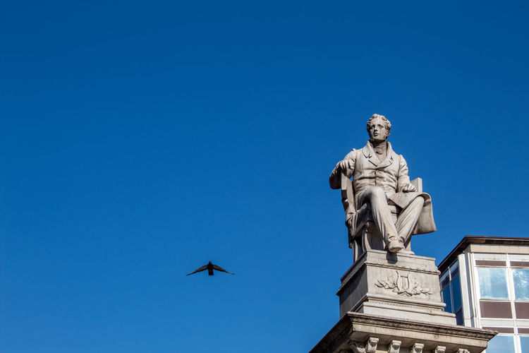A dove passes flying near the statue in piazza stesicoro
