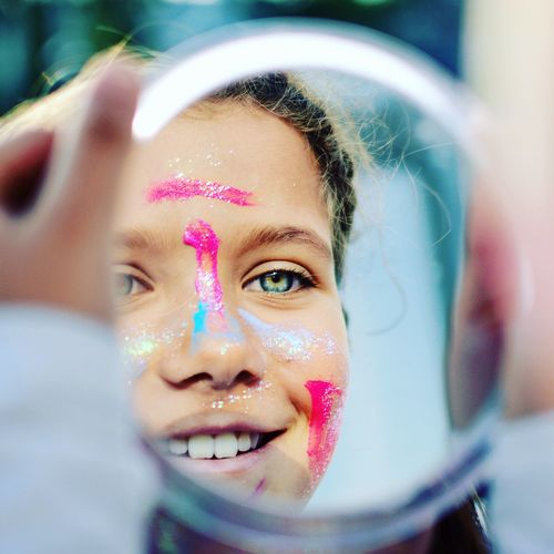 Reflection of girl with face paint smiling on mirror