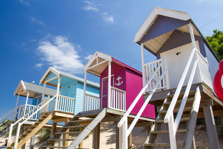 Rows of colourful beach huts on wooden stilts on the sandy beach at Wells Next The Sea in Norfolk, UK on a bright sunny day with blue sky above. Architecture Beach Beach Hut Beach Huts Beach Life Beachphotography Building Exterior Built Structure Colourful Day No People Norfolk Outdoors Resort Rows Sand Sky Summer Summertime Travel Travel Destinations Uk Vacation Vacations Wells Next The Sea