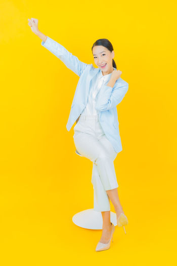 Portrait of young woman standing against yellow background