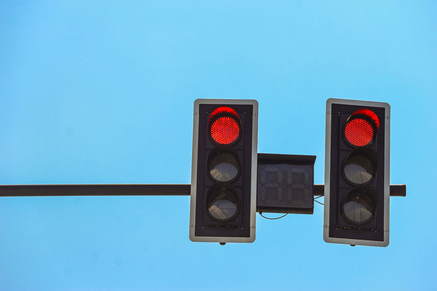two red traffic light on blue sky Blue No People Road Signal Red Light Light Stoplight Illuminated Communication Lighting Equipment Sign Technology Sky Copy Space Guidance Control Close-up Red Clear Sky Day Low Angle View Blue Background Trafic Light Trafficlight Space