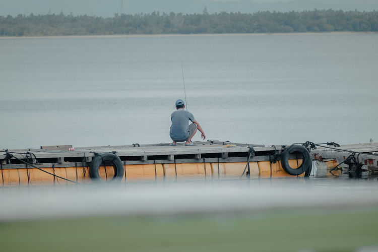 Rear view of man fishing while crouching on pier