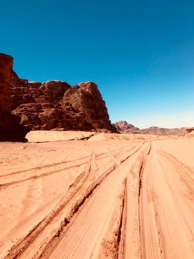 Panoramic view of desert land against clear blue sky