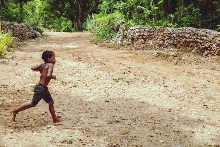 Full length of shirtless boy running on street