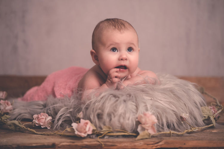 Portrait of cute baby girl sitting at home