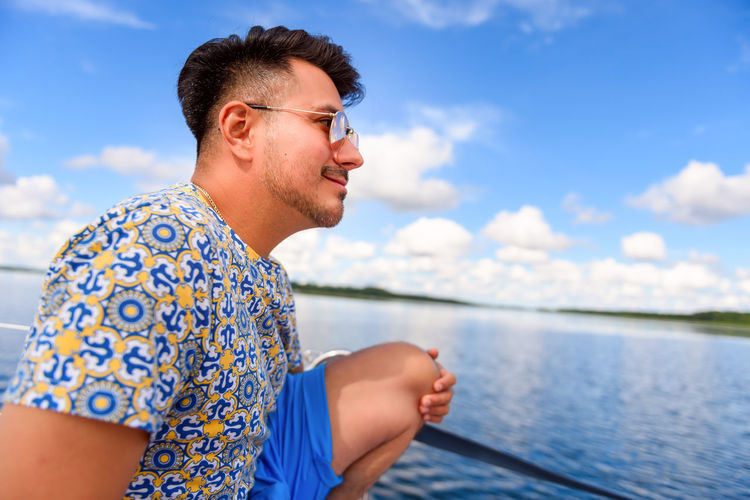 Young man seating on a main deck of a sailboat, sailing on a lake. summer vacations leisure activity