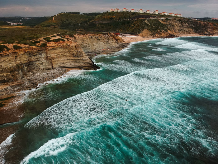 Aerial view from a surf spot with waves and a group of surfers in Ribeira d' Ilhas beach in Ericeira, Portugal Portugal Surf Aquatic Sport Beach Beauty In Nature Day Flowing Flowing Water Motion Nature No People Outdoors Power In Nature Rock Scenics - Nature Sea Sport Spot Tourism Tranquil Scene Travel Travel Destinations Turquoise Colored Water Waterfall