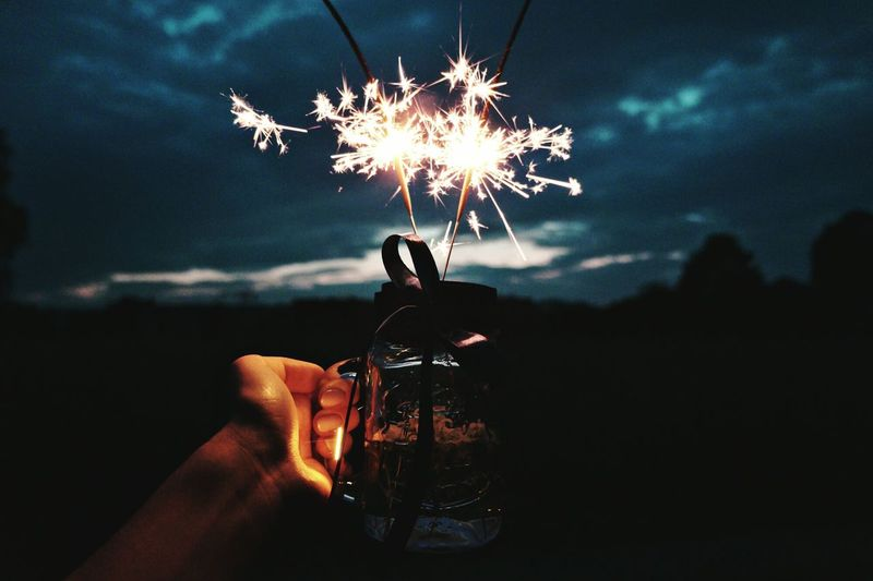 Close-Up Of Hand Holding Drink With Sparklers