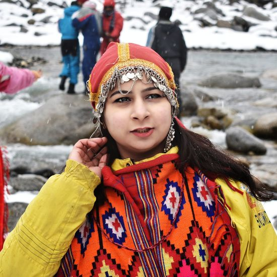 Young woman in traditional clothing standing outdoors