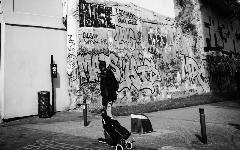 Full length of man walking on graffiti in city
