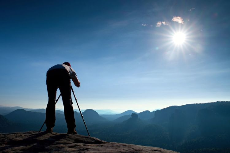 Professional photographer with tripod on cliff and thinking. dreamy fogy land, beautiful valley