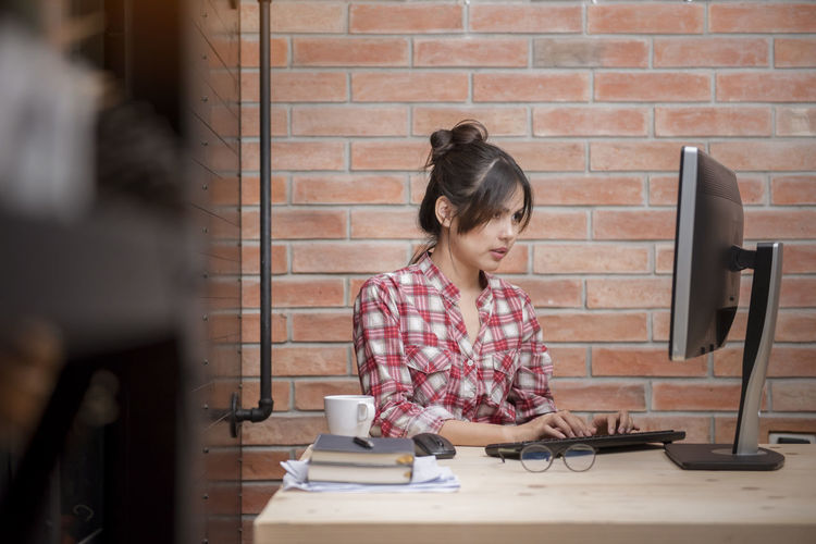 Young Businesswoman Working At Computer Desk Against Brick Wall In Office