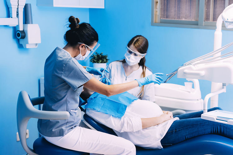 Female Dentists Examining Woman At Clinic