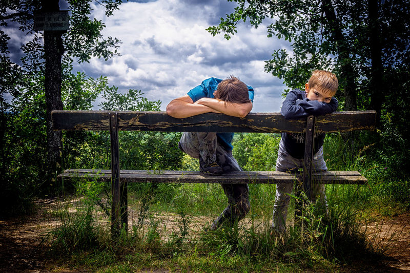 Bored Friends Leaning On Wooden Bench By Trees Against Cloudy Sky