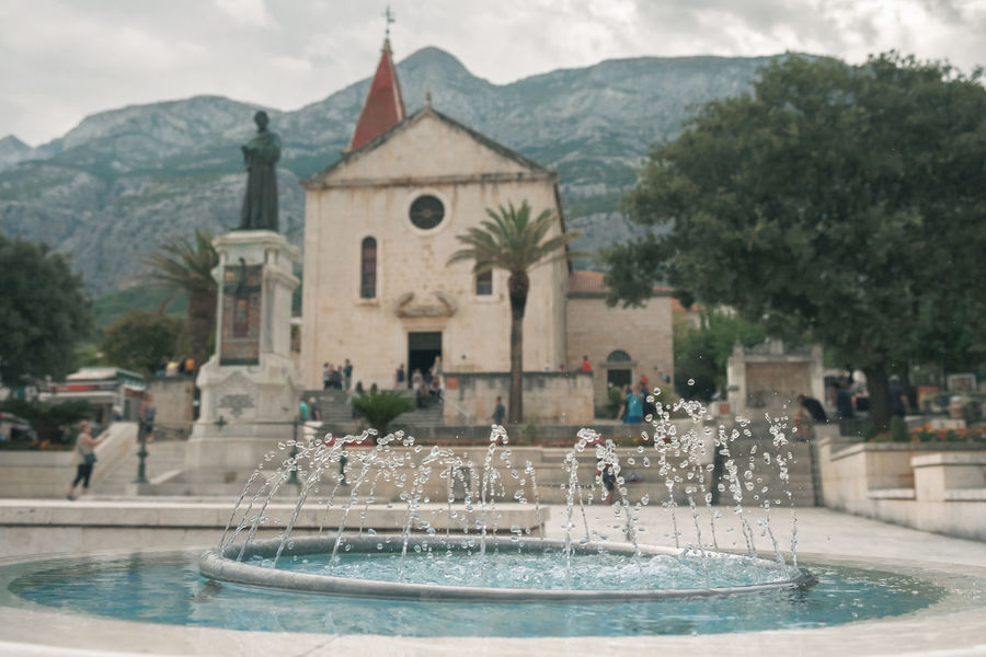 Cathedral Church City City Life Cityscape Fountain Mediterranean Culture Architecture Building Exterior Built Structure Catholicism Day Mountain Mountain Range Outdoors Pine Tree Praying Real People Religion Selective Focus Spirituality Spray Tourism Town Water